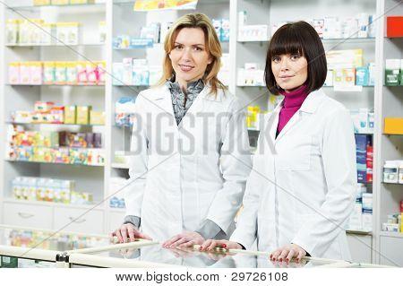Two cheerful pharmacist chemist woman standing in pharmacy drugstore