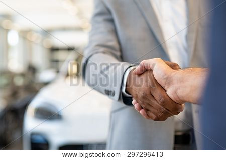 poster of Closeup of a salesman shaking hands with his client after selling him a car at the dealership. Hands