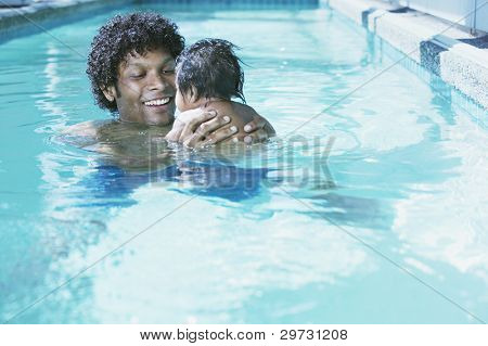 Father with baby in swimming pool