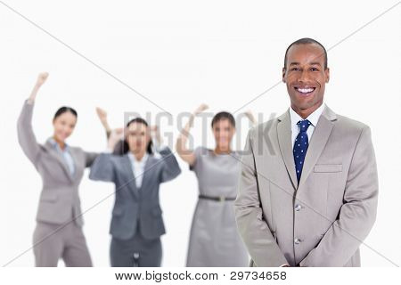 Close-up of a happy businessman smiling with enthusiastic co-workers raising their arms in the background