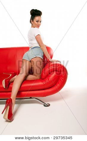 Beautiful pert leggy retro pinup girl in shorts kicking up her heels on a red leather sofa.