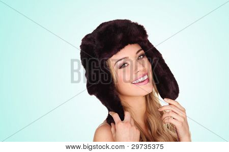 Attractive young woman wearing a winter fur hat with earflaps giving a beautiful smile