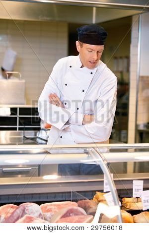 A butcher looking at the available meat in a grocery store