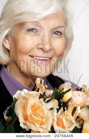 Senior woman portrait, smiling with a bunch of roses