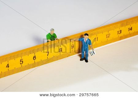 Two Workmen Figurines With A Ruler