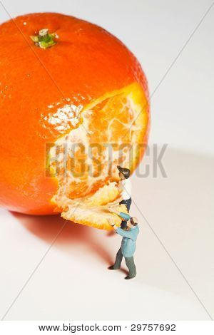 Two Figurines Peeling An Orange