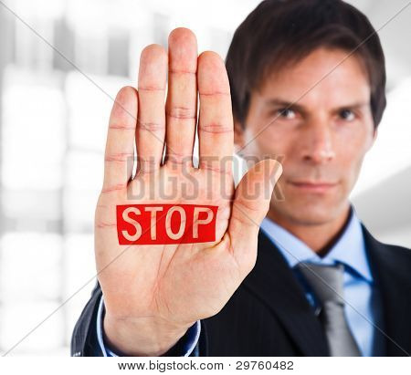 Serious businessman making stop sign
