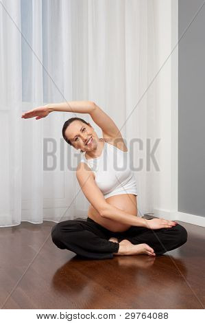 healthy pregnant woman doing yoga at home