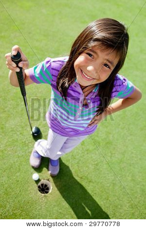 Young female golf player standing next to the hole