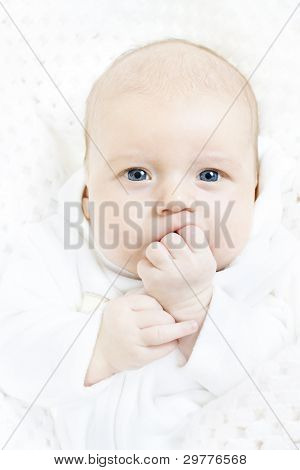 Newborn Baby Closeup Portrait Over White Soft Background. Indigo Eyes Looking At Camera