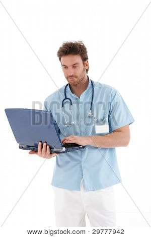 Young doctor standing, working on laptop, looking at screen.?