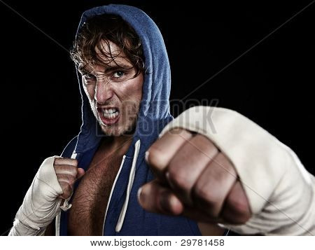 Boxer - street fighter in hoody fighting aggressive looking angry at camera hitting with hand wraps tape on hands. Young caucasian male fitness model isolated on black background.