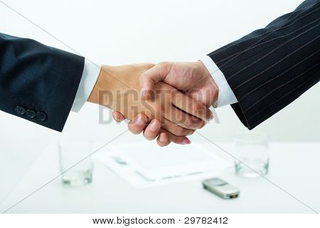 Close-up of two shaking hands over workplace with business documents on it