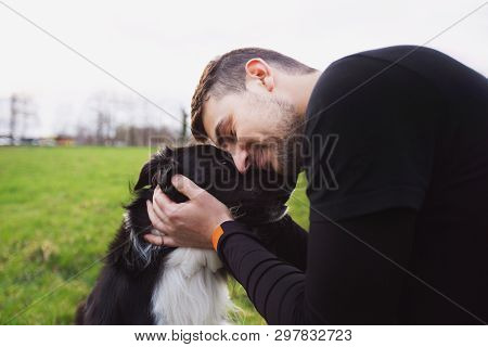 poster of Man Embracing His Border Collie Dog . Young Owner Hugs His Pet. Friendship Between Owner And Dog. An