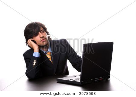 Young Business Man Working With His Laptop And Calling On Cellphone