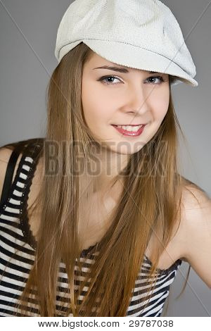 attractive brunette in a white cap and a striped vest