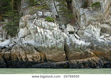 Rocks Create A Wall Of Stone In Beautiful Colors At Water's Edge Of Glacier Bay Near Skagway - Alask