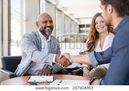 poster of Smiling couple buying a new auto at car showroom. African salesman making handshake with young man p