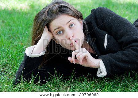 Portrait of a beautiful young fresh girl hushing
