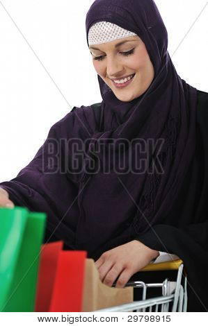 happy muslim woman with shopping cart  over white
