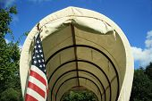 pic of covered wagon  - Covered wagon upclose with an American Flag - JPG