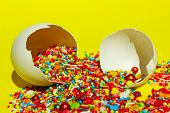 Multicolored Candy Sweets On Yellow Background. Closeup Of Multicolored Small Candies In The Eggshel poster