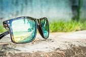 Fashionable Sunglasses. Sunglasses With Mirrored Lenses. Reflection Of The Beach And Tropical Palm T poster