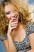stock photo of beautiful women  - A laughing fashion model with curly hair on grey background - JPG
