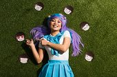 Asian Anime Girl In Purple Wig With Emoticons Lying On Grass poster