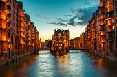 The Warehouse District Speicherstadt During Twilight Sunset In Hamburg, Germany. Illuminated Warehou poster