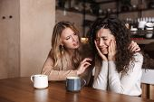 Two upset young girls friends sitting at the cafe table, drinking coffee, cheering each other up poster