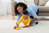 childhood, kids and people concept - happy african american mother and her baby son playing with toy poster