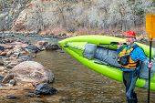 happy senior paddler carrying inflatable whitewater kayak on a shore of mountain river in early spri poster