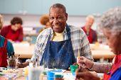 Portrait Of Retired Senior Man Attending Art Class In Community Centre poster
