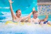 Thrilling expression of a father and his son as they splash down a water slide at an amusement park  poster