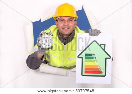 Tradesman holding an energy efficiency rating chart and an alarm clock