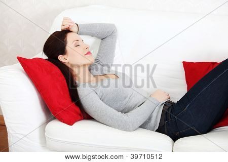 Young beautiful woman lying on a couch, holding her hend on the forehead.