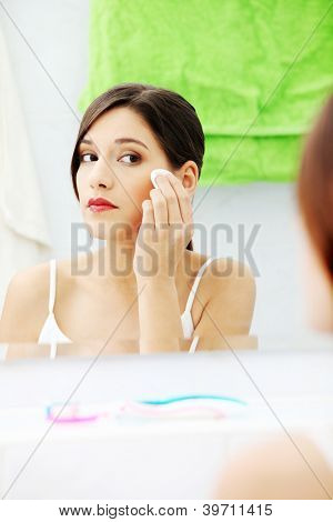 Young beautiful caucasian woman cleaning her face with cotton pad in the bathroom