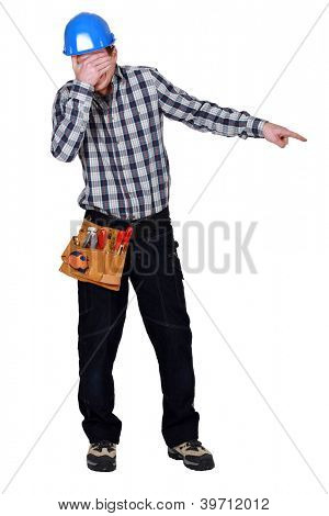 Construction worker covering his eyes and pointing at something