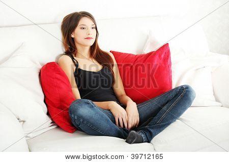 Triste joven sentado en el sofá en casa