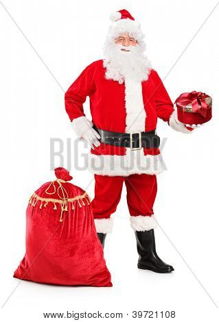 Full length portrait of a Santa Claus holding a gift and bag full of presents next to him isolated on white background