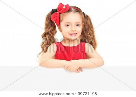A small girl posing behind a blank panel