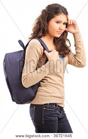 A sad female teenager with a school bag on her back posing isolated on white background