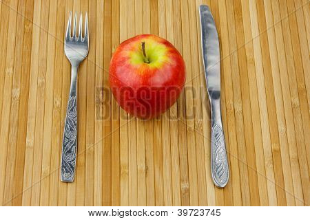apple lying on a bamboo napkin with cutlery