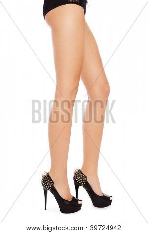 Long beautiful legs of slim sexy woman in stylish spike shoes, over white background
