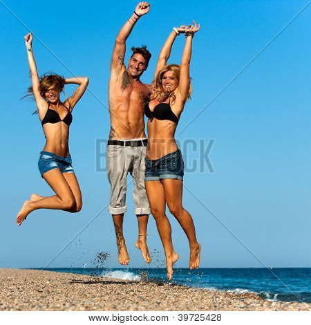 Energetic Friends Jumping On Beach.