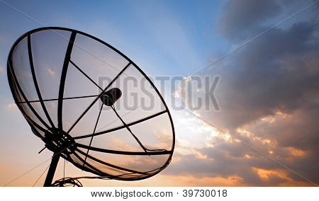 Big telecommunication satellite dish over sunset sky