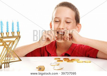 Little boy playing dreidel and eating chocolate Hanukkah gelt.  White background.