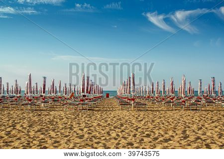 Withdrawn Umbrellas And Sunlongers On The Sandy Beach