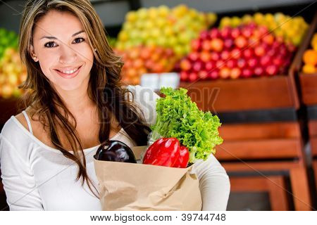 Happy woman at the local market buying groceries